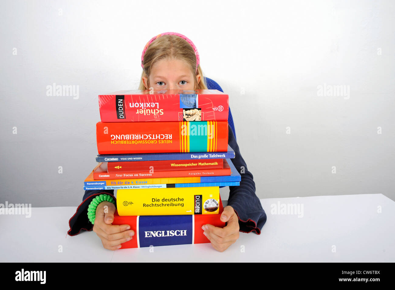 school girl with a stack of school books - Stock Image