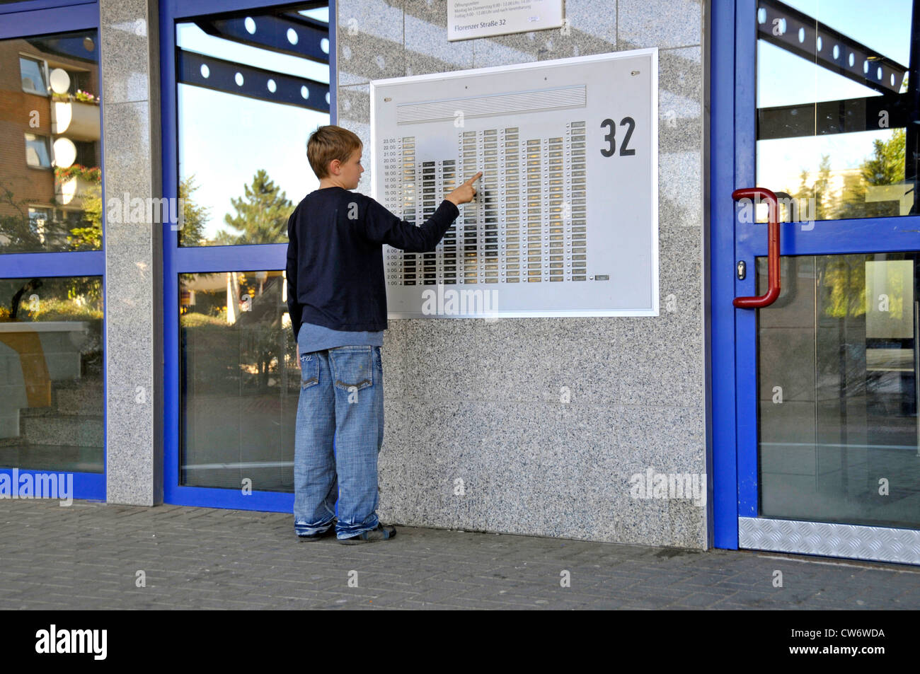 9 years old boy at a door plate of a multi-story building in Chorweiler, Germany, North Rhine-Westphalia, Cologne - Stock Image