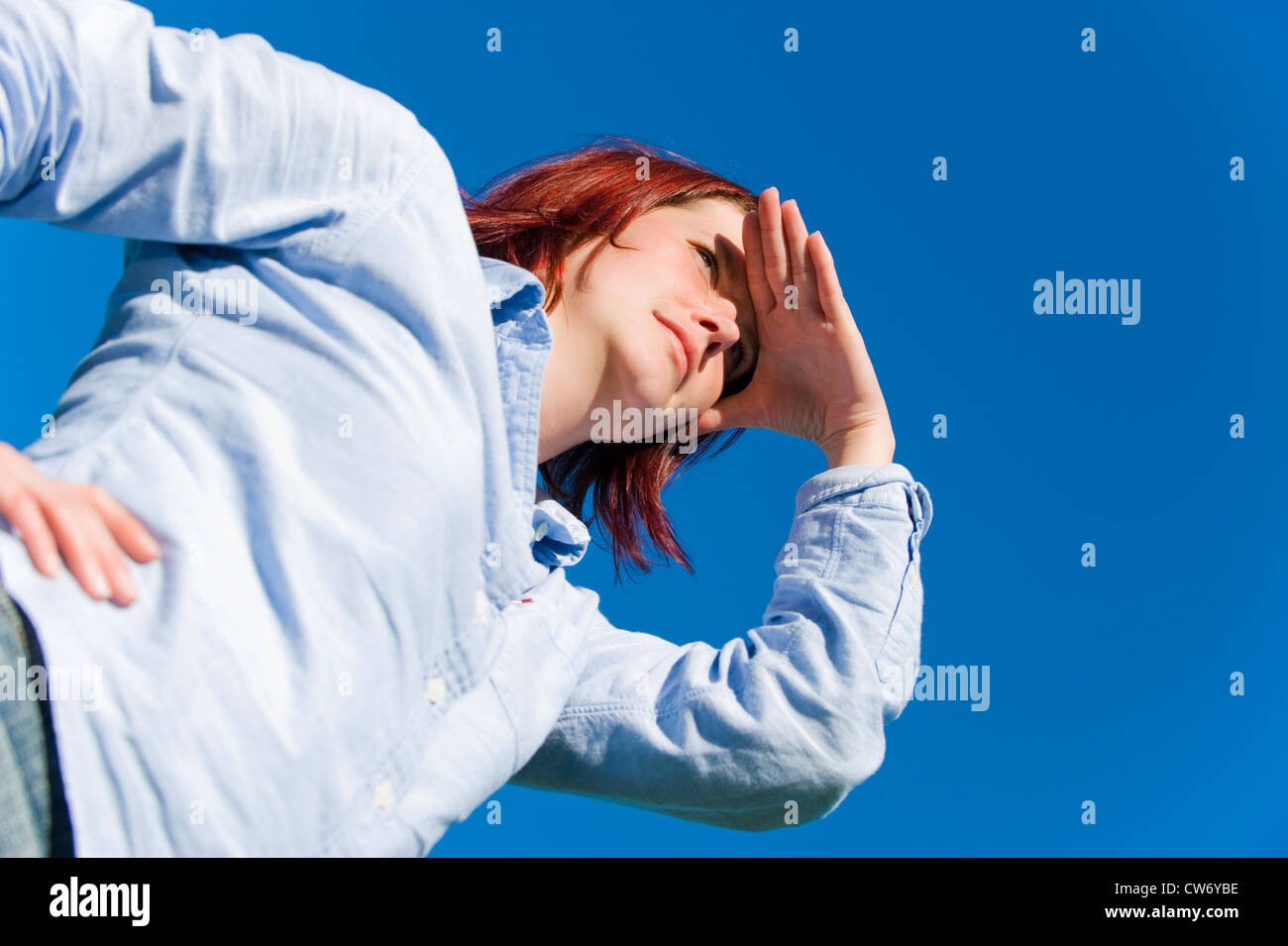 Worms Eye View At A Red Haired Young Woman In Front Of Blue Sky Stock Photo Alamy