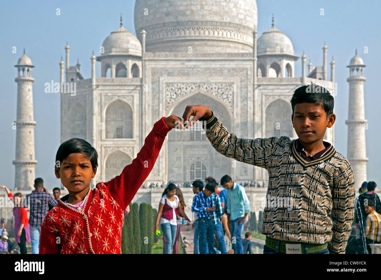 Indian children posing in front of the Taj Mahal, white marble palace in Agra, Uttar Pradesh, India - Stock Image