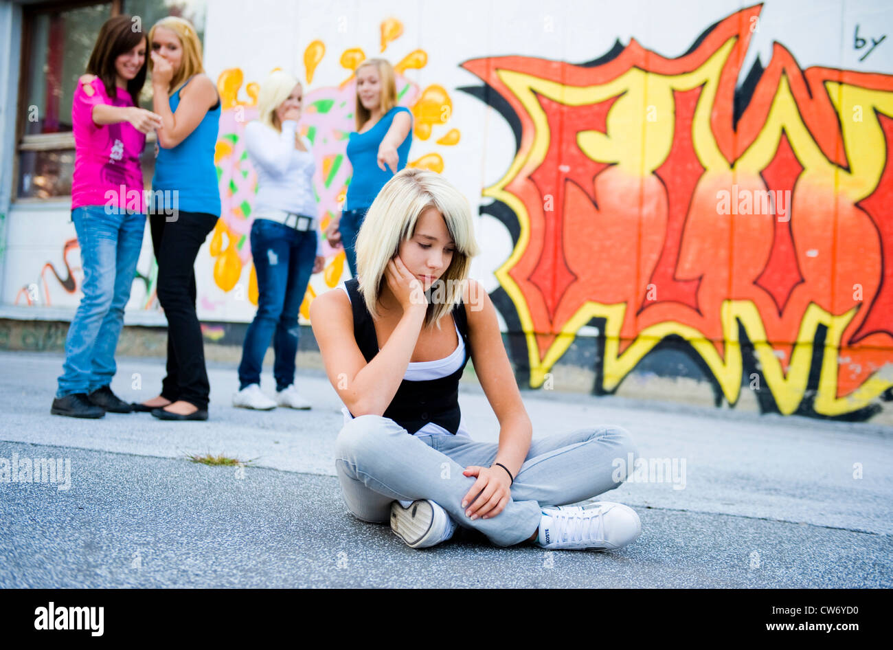 schoolgirl sitting in the schoolyard frustrated, schoolmates in the background slagging her off Stock Photo