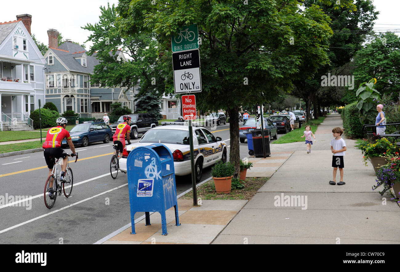 Boy watches bicycle riders in bike lane roll by. - Stock Image
