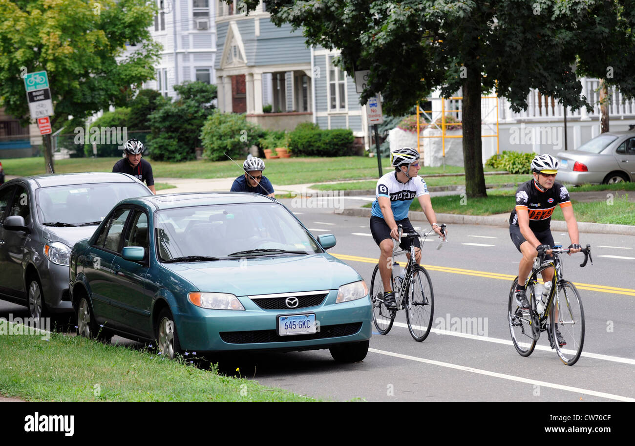 Bicycle riders in bike lane on city street. - Stock Image