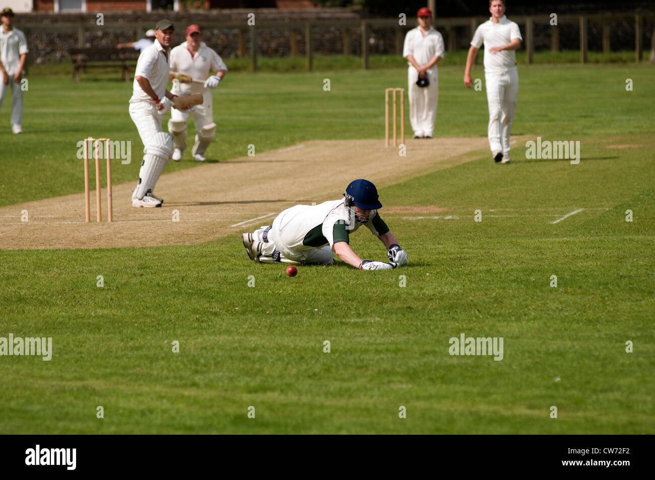cricket match village green play playing players bat batsman bowler wicketkeeper wicket wickets grass green uk english - Stock Image