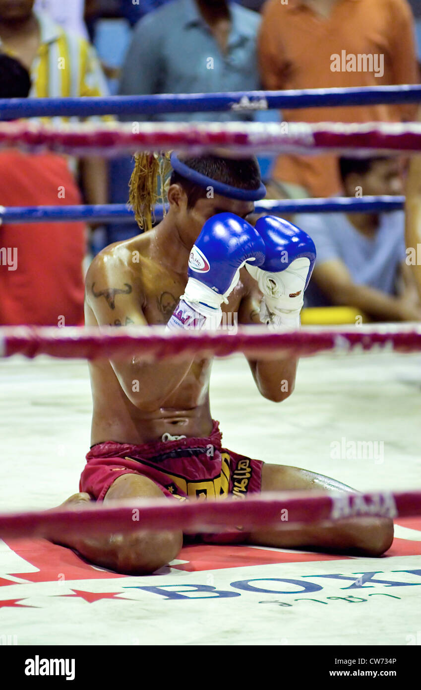 young Muay Thai Boxer concentrating and performing a ritual before a fight, Thailand, Krabi - Stock Image