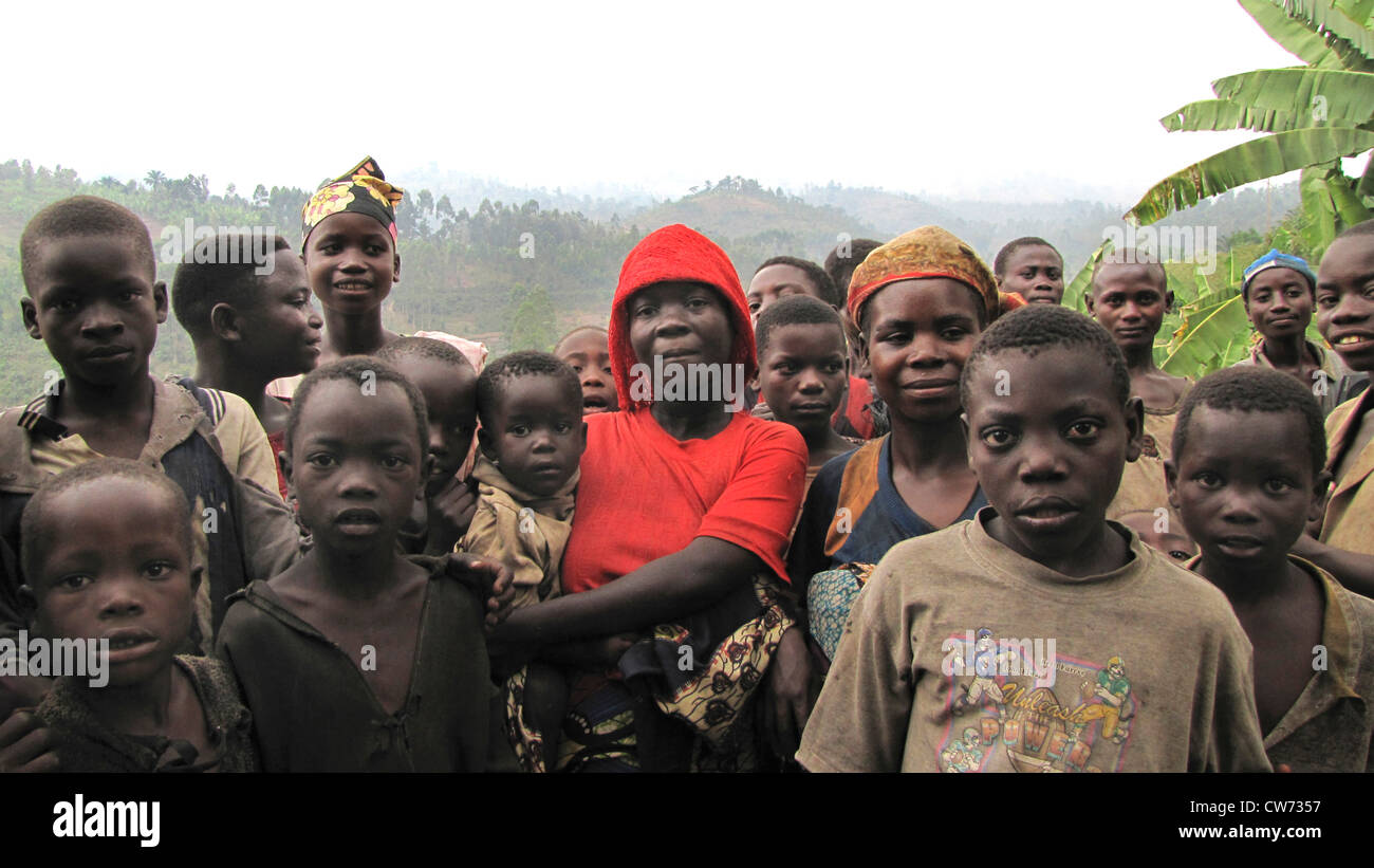 group photo of members of the minority of the Batwa in front of hilly forest landscape isolitad from infrastructure, Stock Photo