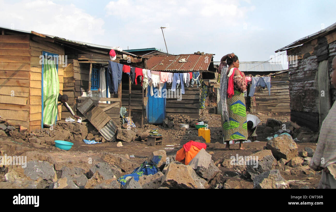 woman hanging up washing in the slums of the city of Goma, being called the 'burned quarter' ('quartier - Stock Image