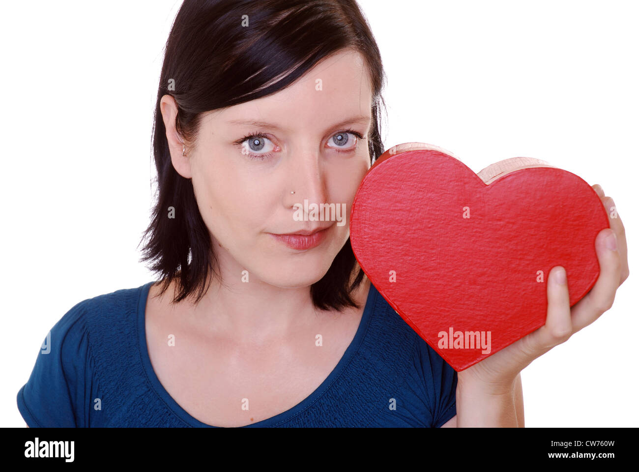 Woman looks thoughtfull and holds a heartgiftbox in her hand - Stock Image