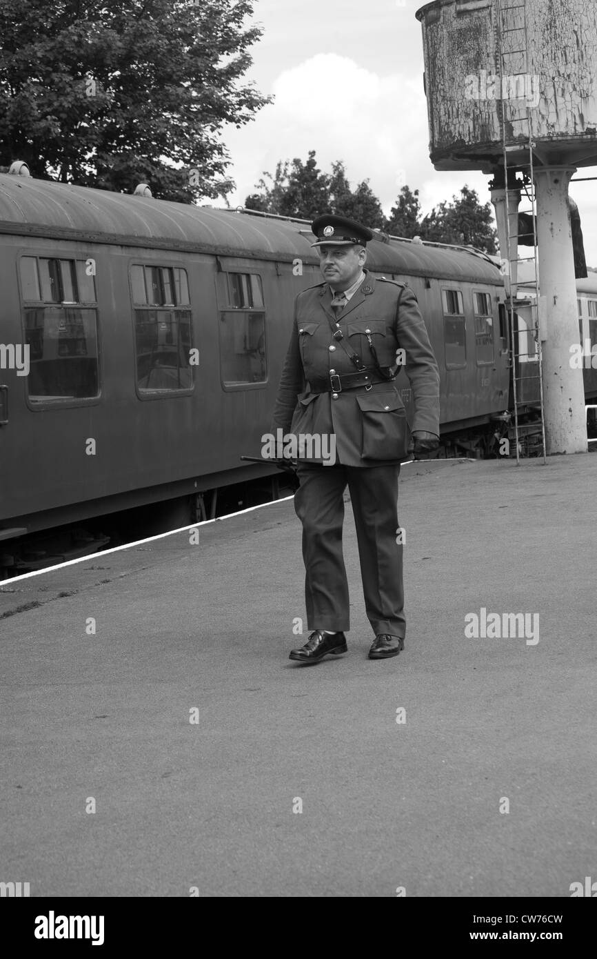 Home Guard Office walking along platform with train - Stock Image