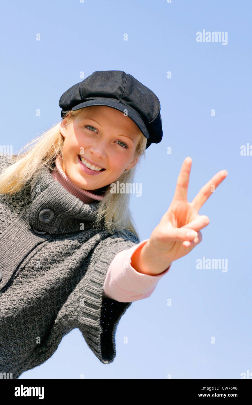 young blond girl with cap, showing the victory sign Stock Photo