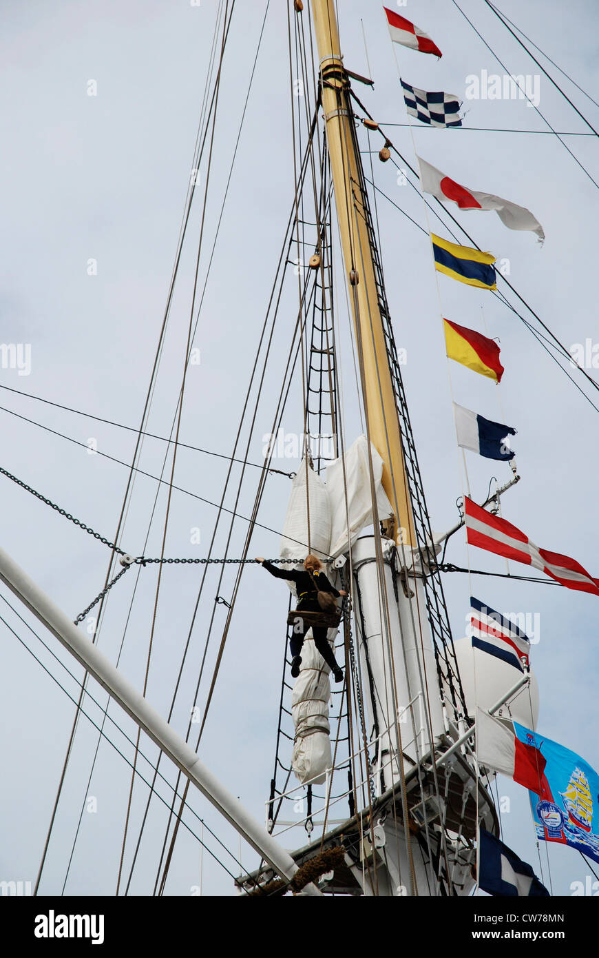female sailor climbing in rigs of tall ship - Stock Image