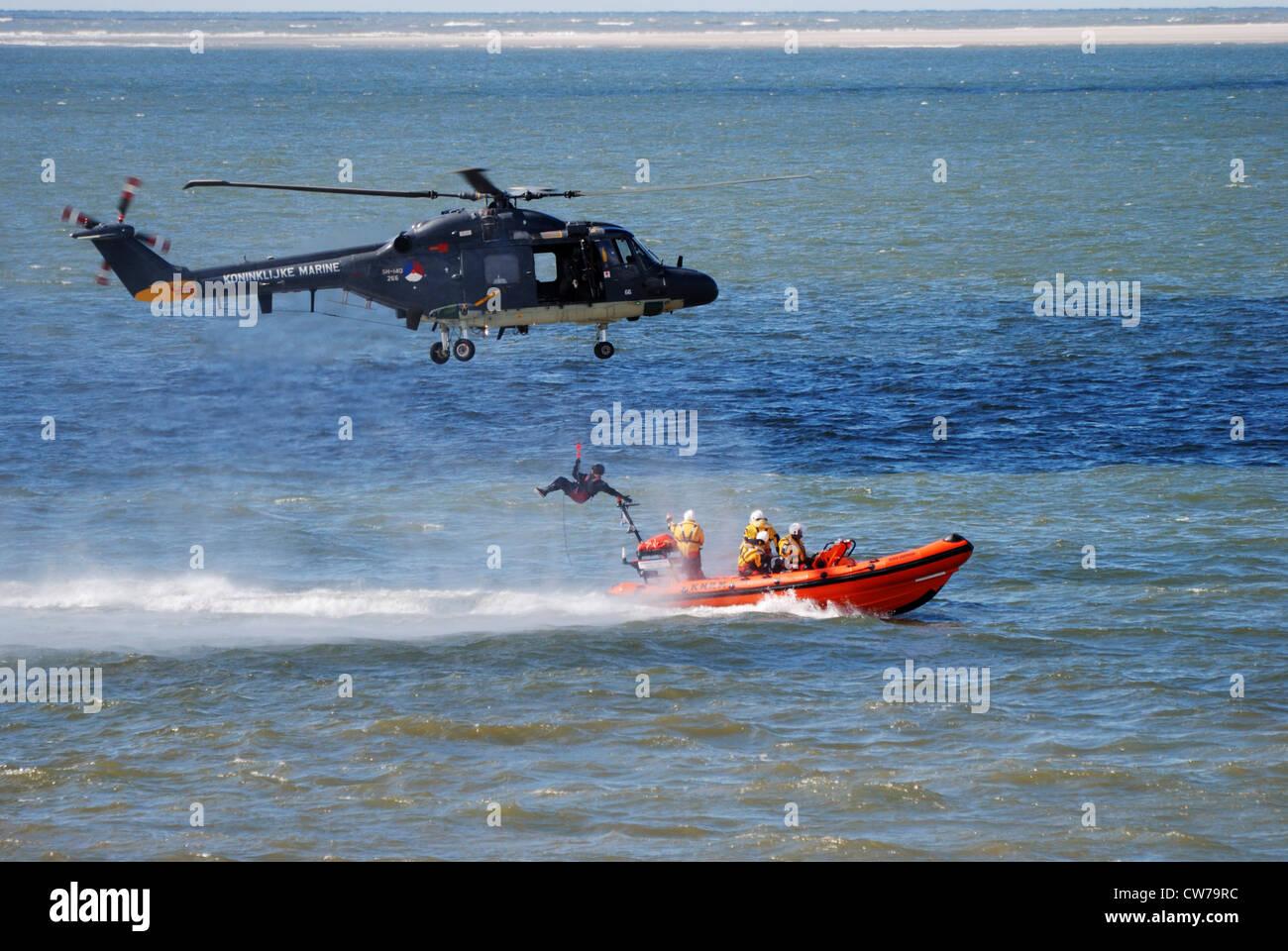helicopter flying life-saver to speeding rubber boat, Netherlands, Den Helder - Stock Image