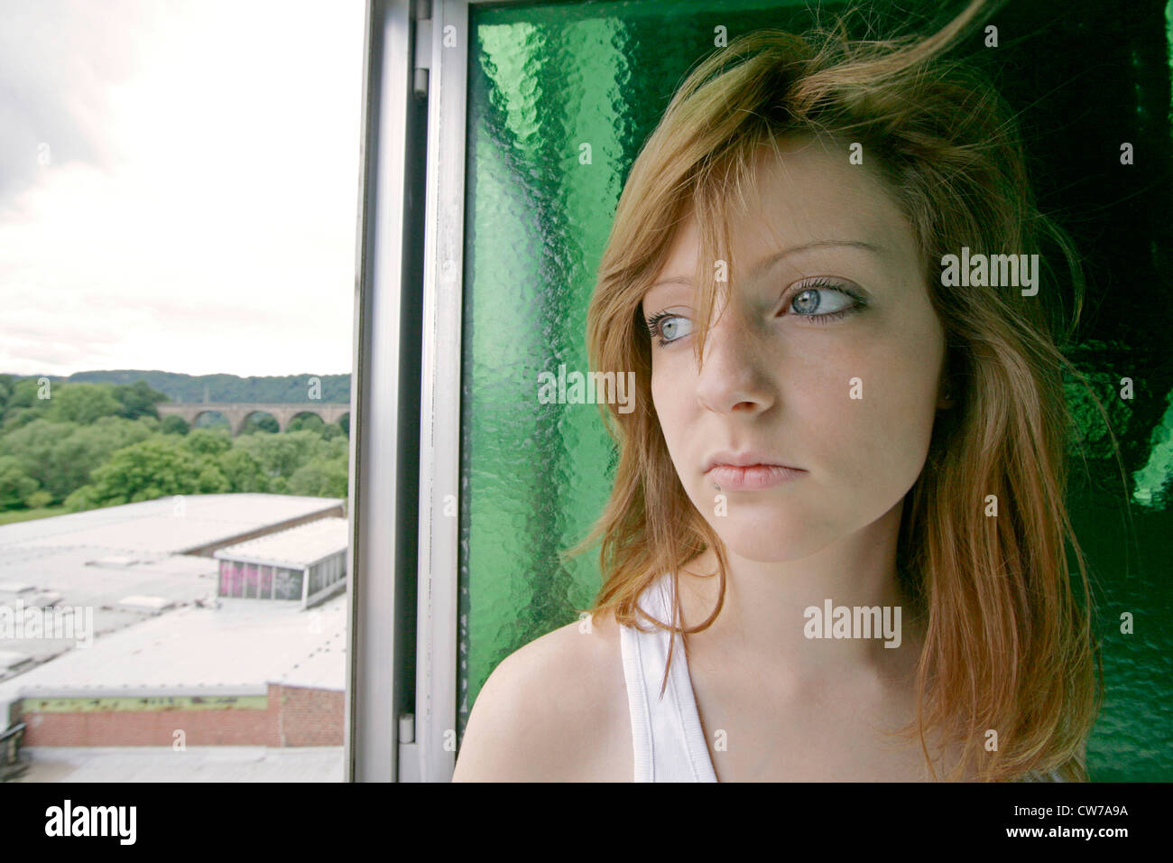 melancholy redheaded young woman looking out of opened window, Germany Stock Photo