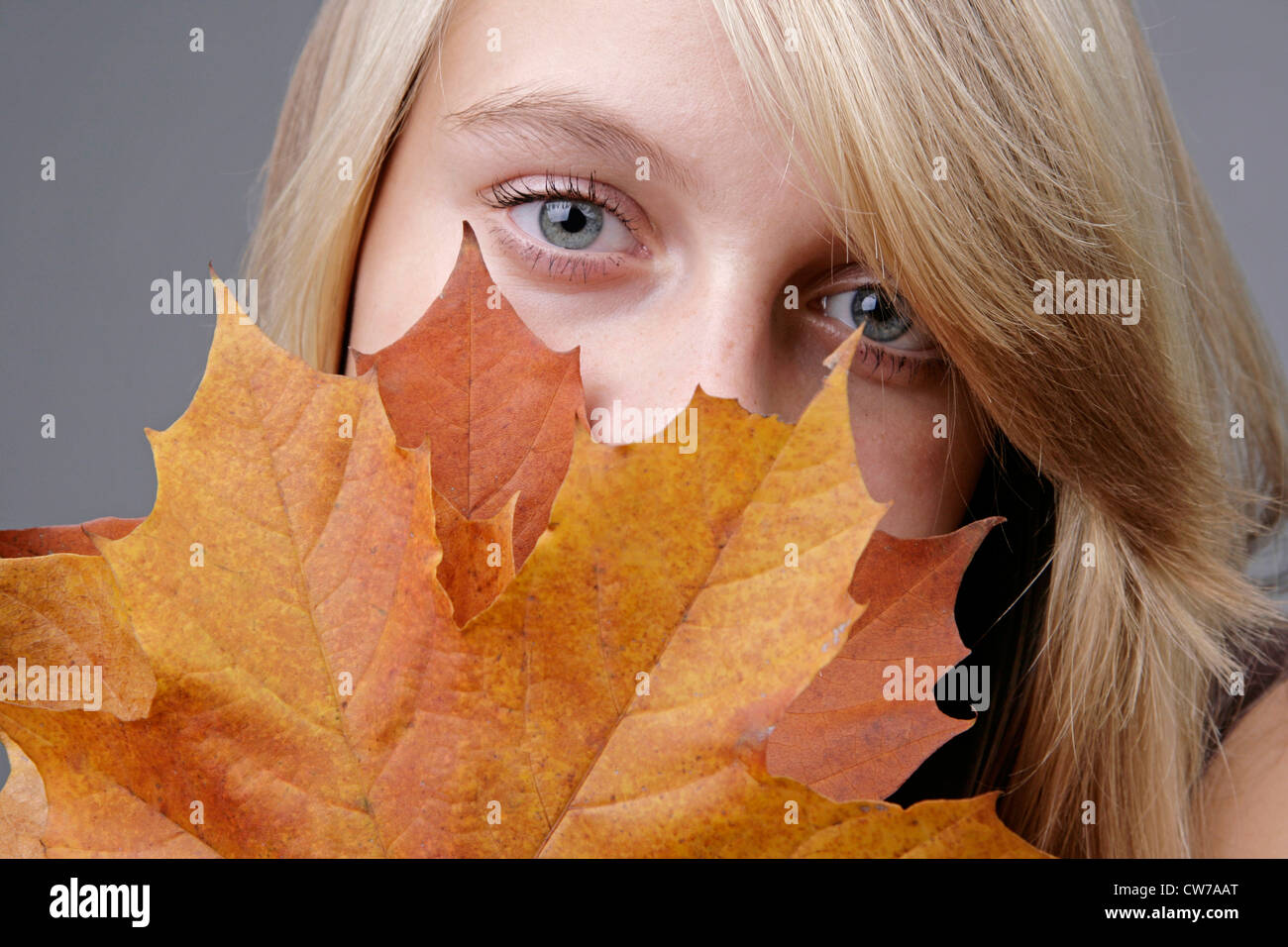 portrait of young blond woman behind autumn leaves, Germany Stock Photo