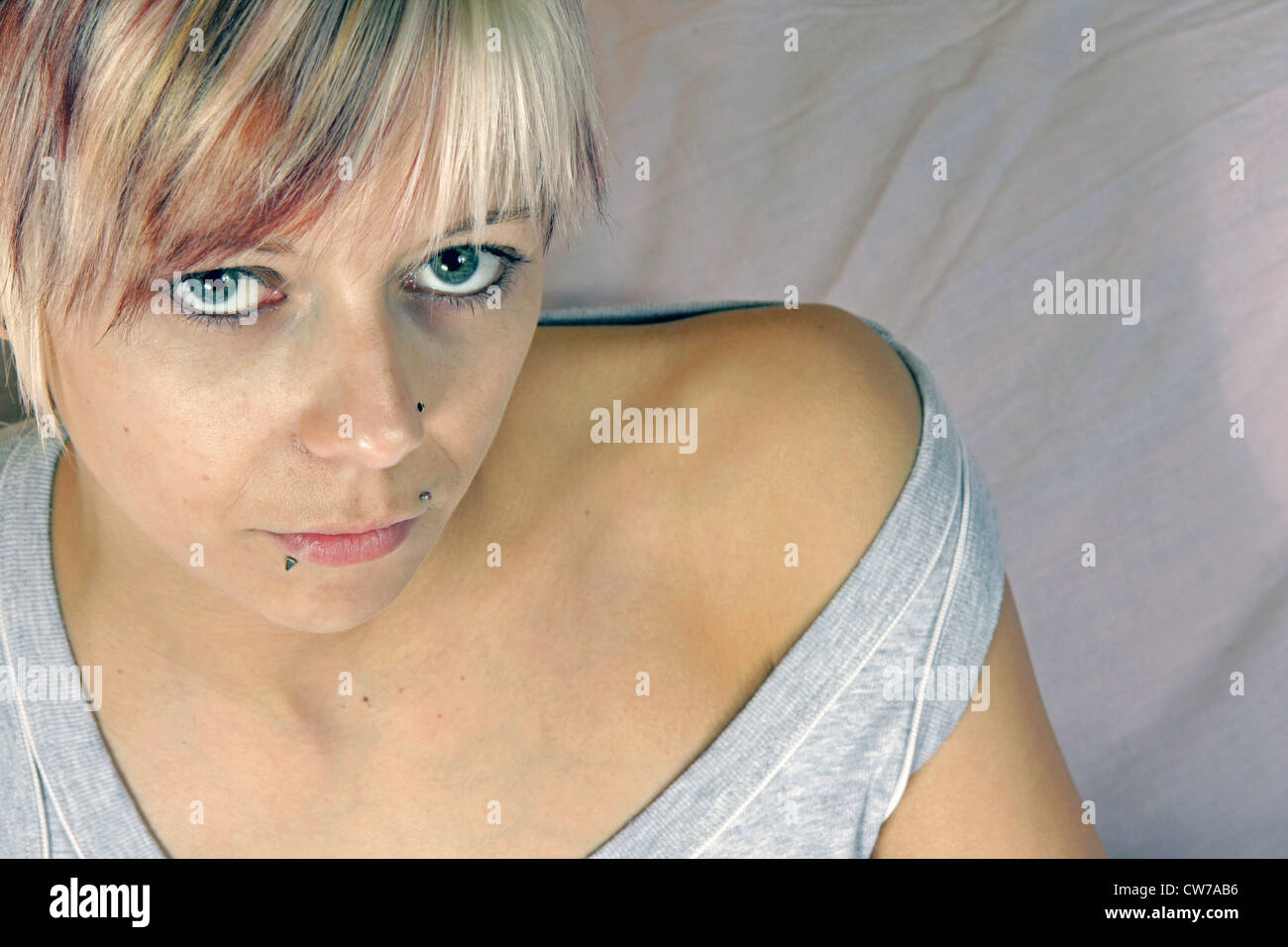 young woman with trendy coloured hair lying in bed, Germany Stock Photo