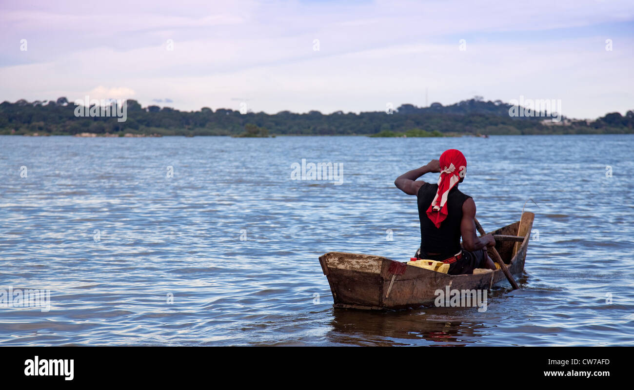 Muscular young fisherman riding his boat on Lake Kivu, Uganda, Entebbe - Stock Image