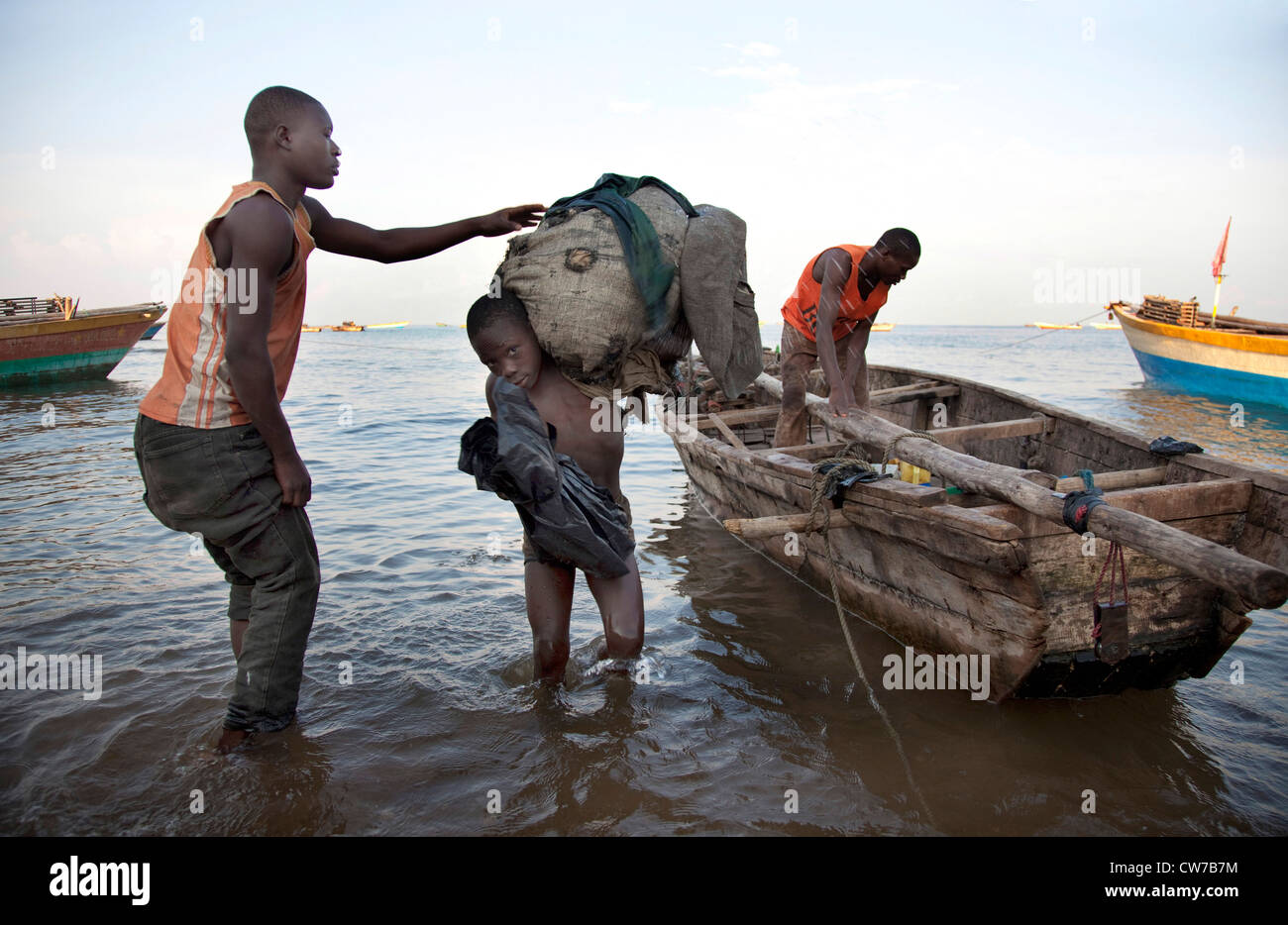 boy carrying a sack full of fishing nets to the shore in the morning after a night of fishing, Burundi, Nyanza Lac, - Stock Image