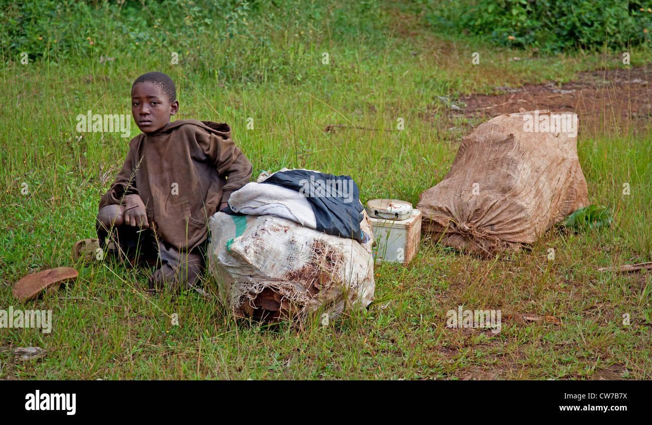 little boy sitting at a roadside beside some possessions before a trip to the capital, Burundi, Ngozi, Ngozi - Stock Image