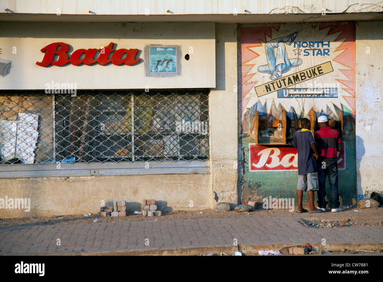 street scene in the capital with little shops near the main market and two men using a public phone, Burundi, Bujumbura - Stock Image