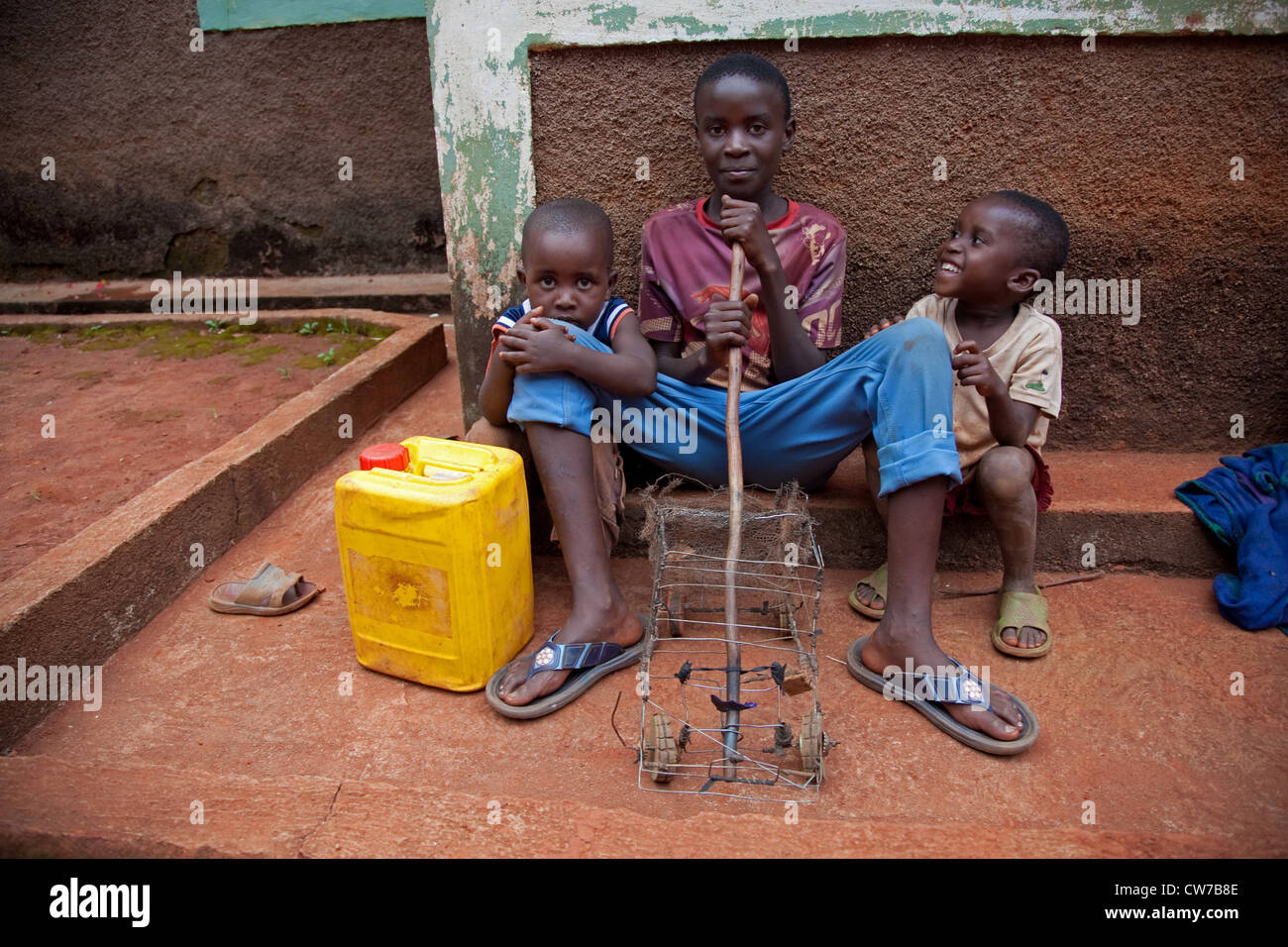 three little children with self-made toy car and water can sitting in front of house wall, Burundi, Gitega - Stock Image