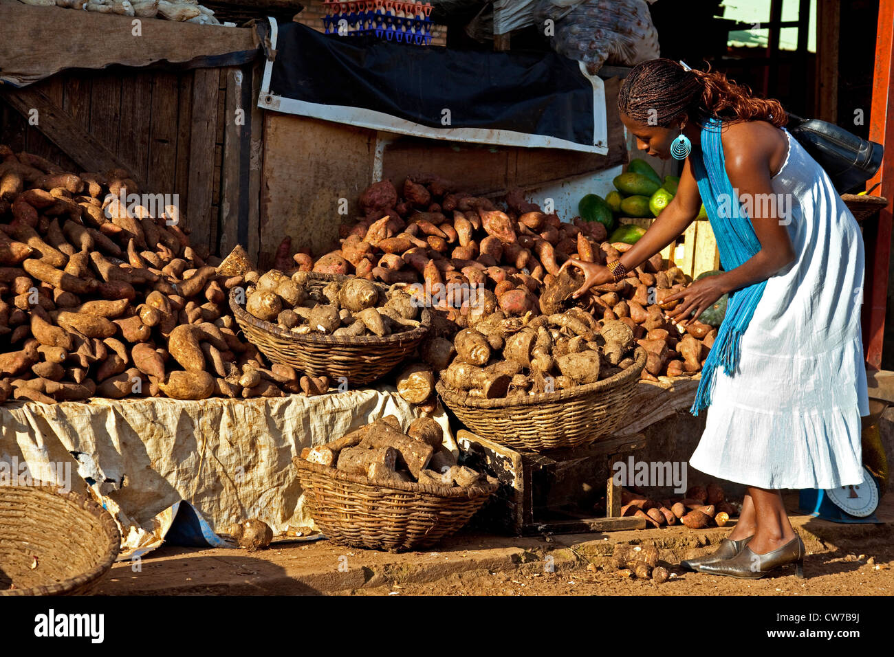 young woman selecting best fruits at market stand with potatoes and yams, Rwanda, Nyamirambo, Kigali - Stock Image