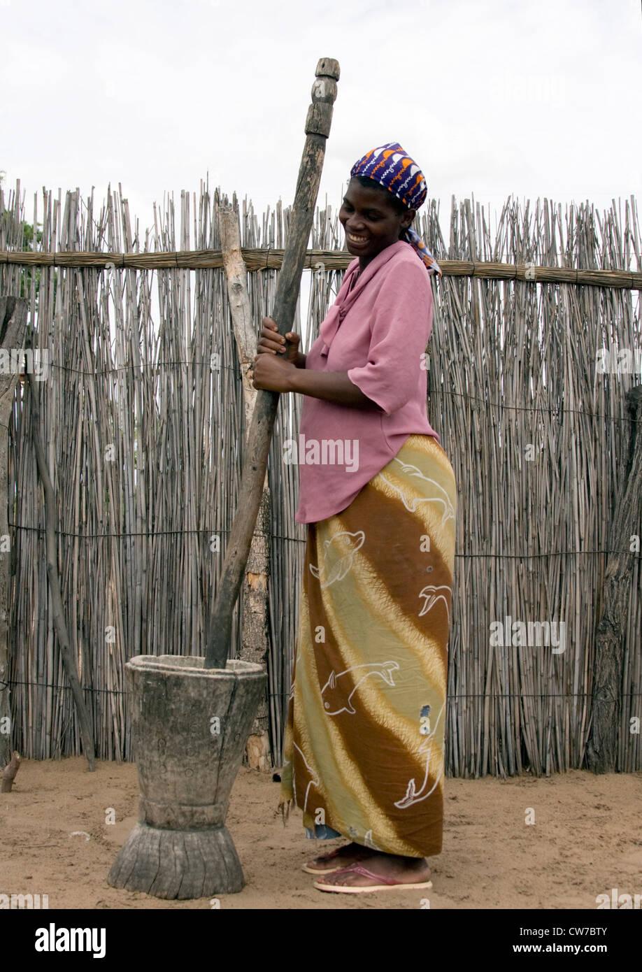 native woman bruising grains , Namibia, Mahango National Park - Stock Image