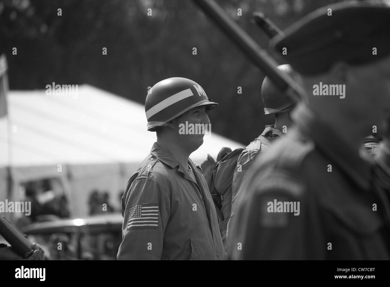 Re-enactor playing 1940's British and American Army Soldiers with others on parade - Stock Image