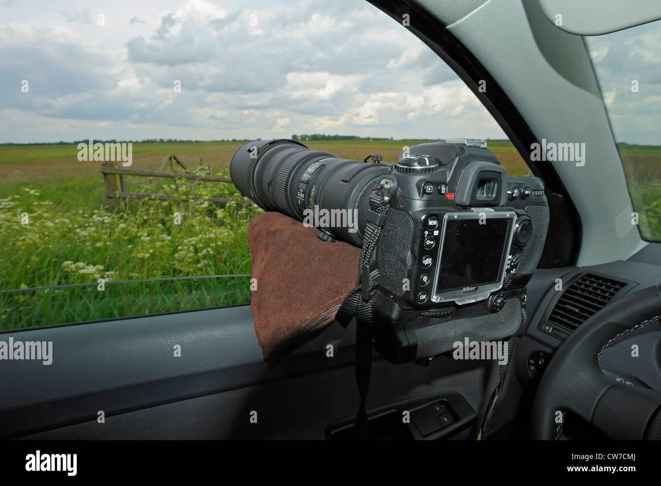 photo camera on bean bag lying in open window of a car, Netherlands, Nijkerk - Stock Image