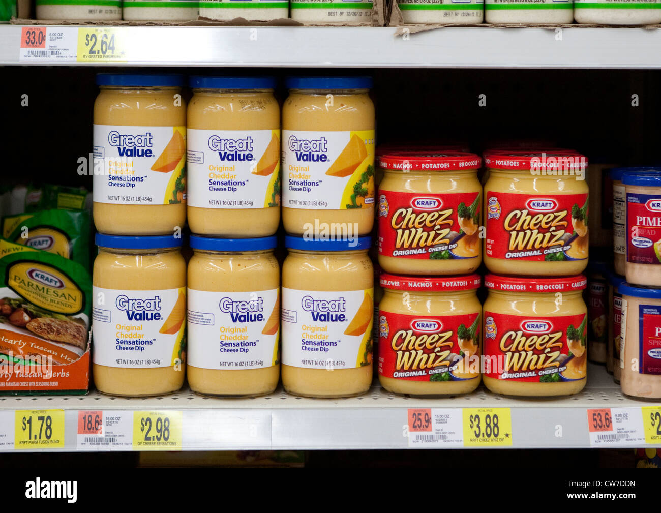 Cheddar cheese dip products on shelve of Wal-Mart store include Kraft name brand Cheez Whiz and comparable product - Stock Image