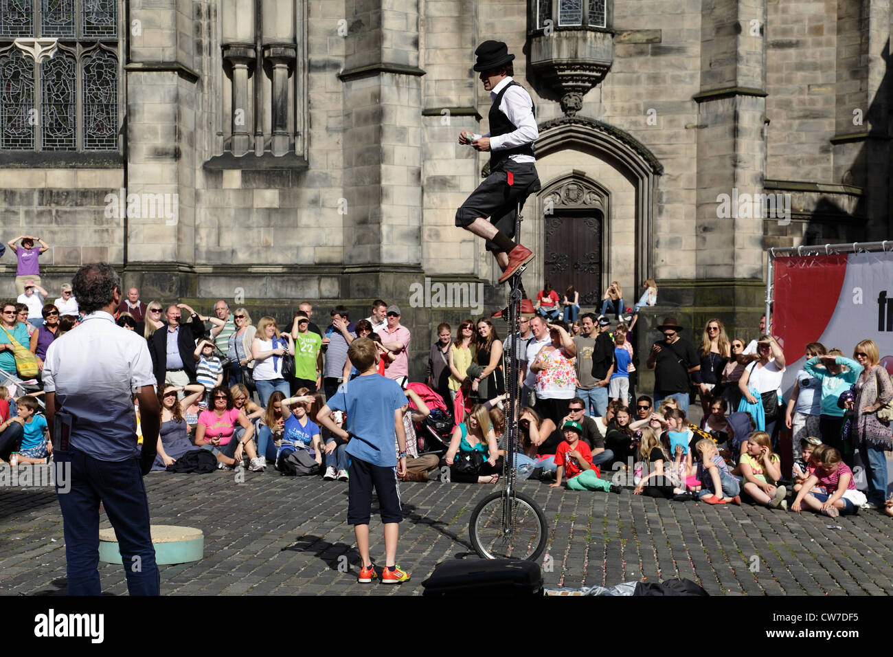 Spectators watching a street performer on a uni cycle at the Edinburgh Festival Fringe in Scotland, UK - Stock Image