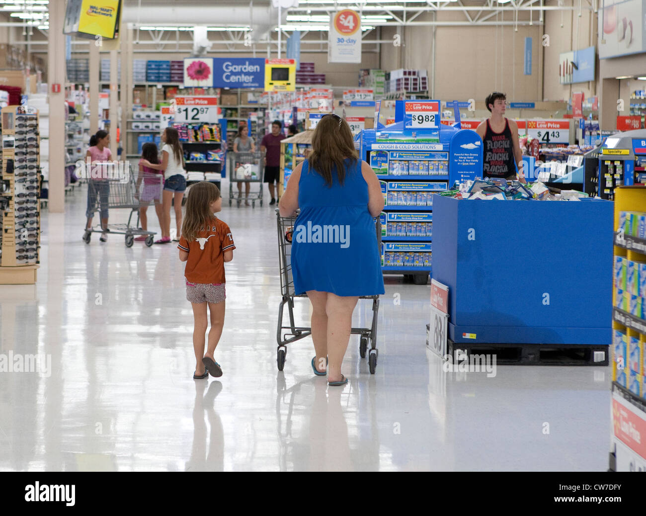 Overweight female customer pushes shopping cart while shopping with daughter at Wal-Mart store in San Marcos, Texas - Stock Image