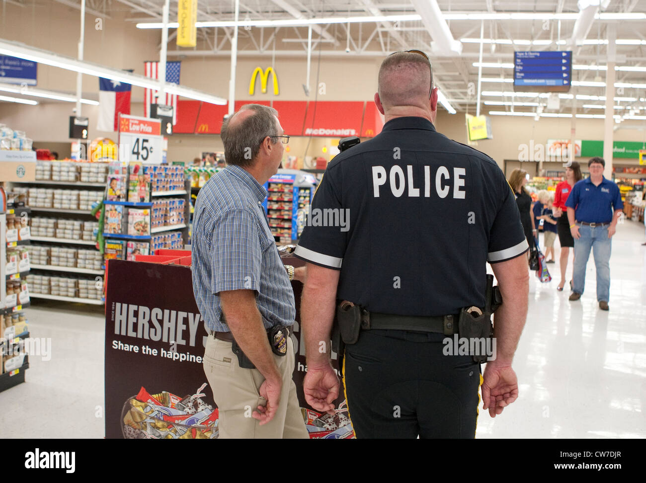 Law enforcement officials, police officer and detective in plain clothing patrol Wal-Mart Supercenter in San Marcos, - Stock Image