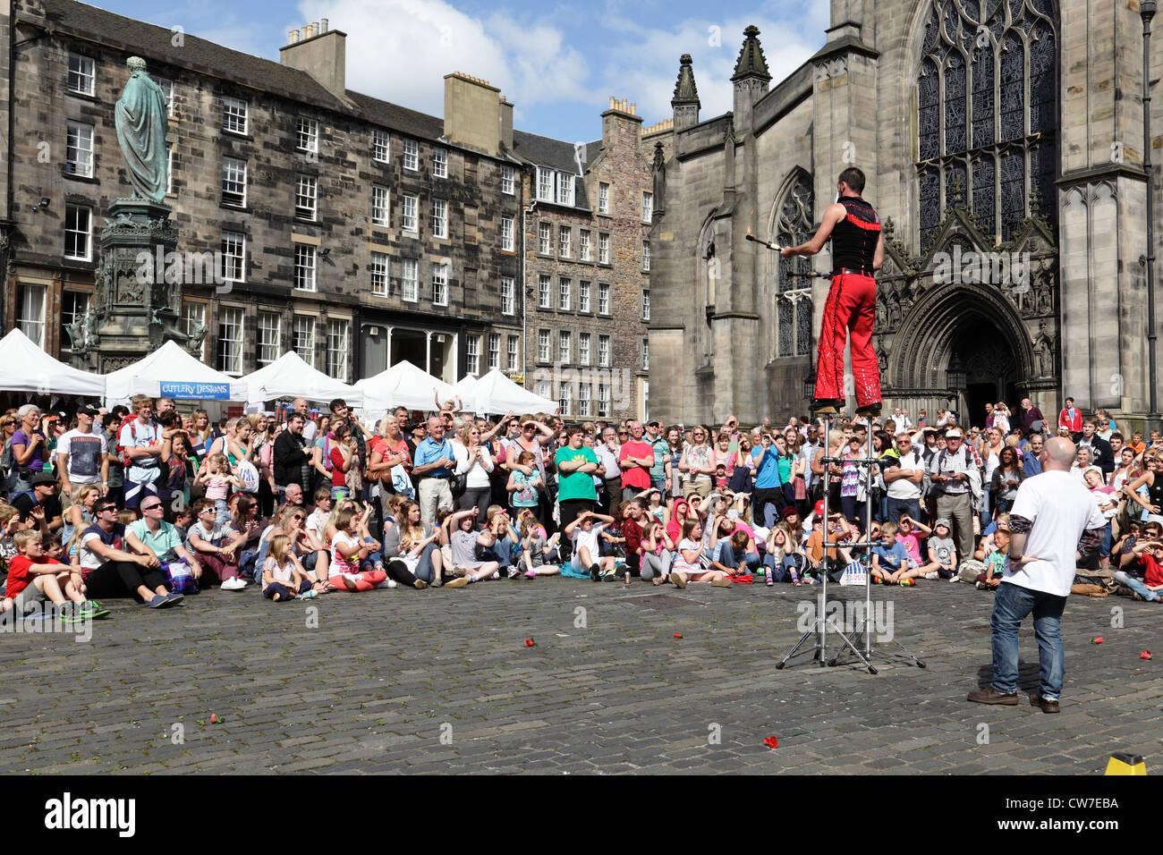 Spectators watching a street performance at the Edinburgh Festival Fringe in Scotland, UK - Stock Image