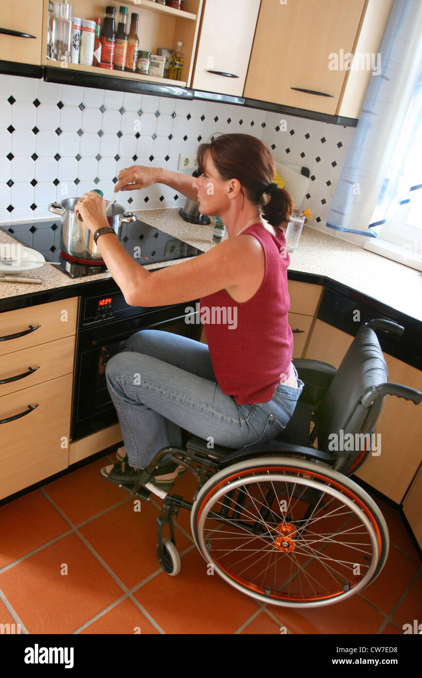 Woman In A Wheelchair Cooking In The Kitchen Stock Photo 49952148