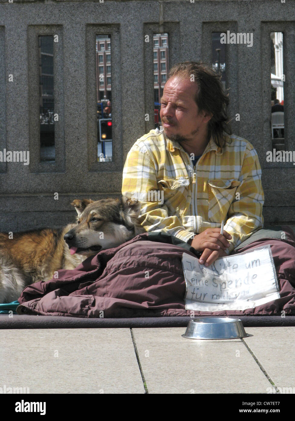 Homeless person with dog is asking for money on a bridge over the Alster in the city of Hamburg, Germany, Hamburg - Stock Image