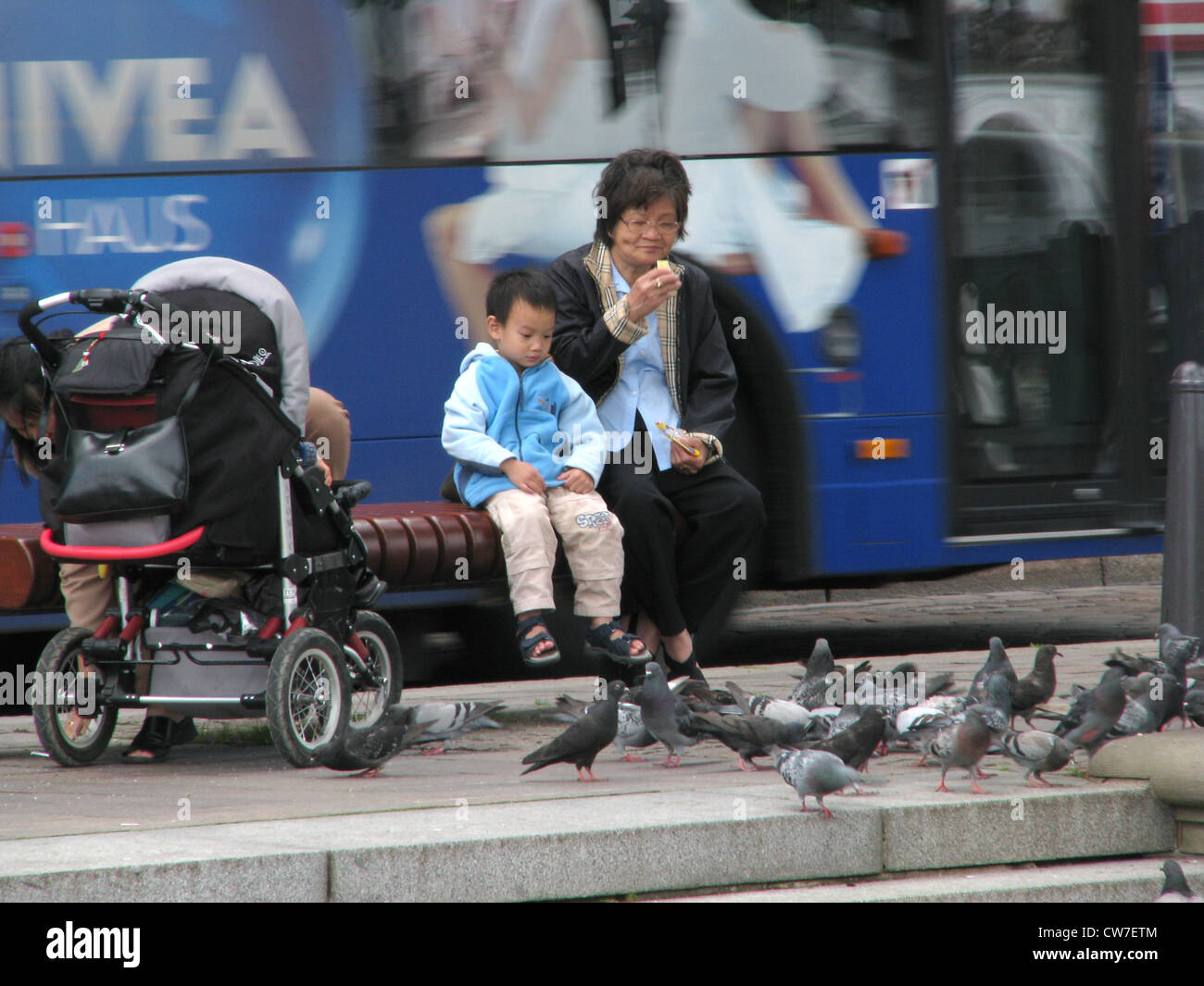 Young boy is watching pigeons eat in the city centre of Hamburg - bus is driving in the background, Germany, Hamburg - Stock Image