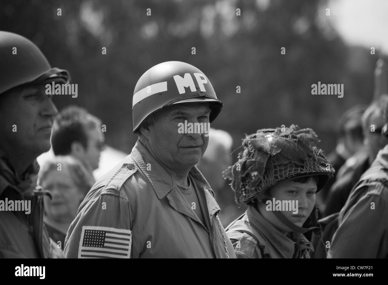 Re-enactor playing 1940's American Soldier with others on parade - Stock Image