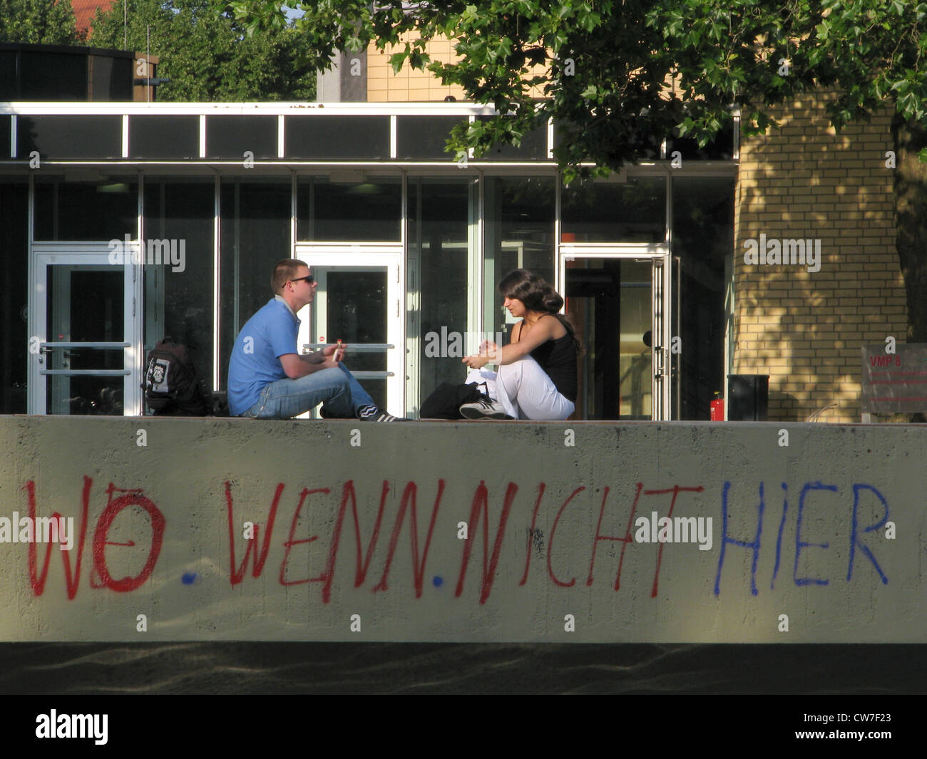 Young students at the university of Hamburg - grafiti saying 'Wo wenn nicht hier' (Where if not here), Germany, - Stock Image