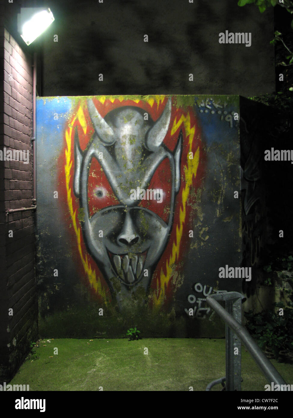 Gloomy grafiti in neon light portrays the devil in a dark backyard, Germany, Hamburg - Stock Image