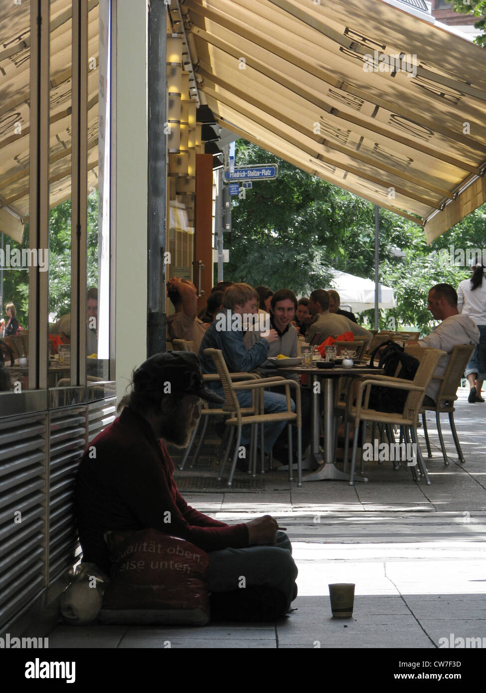 Homeless person asking for money - guests of a cafe in the background, Germany, Frankfurt - Stock Image