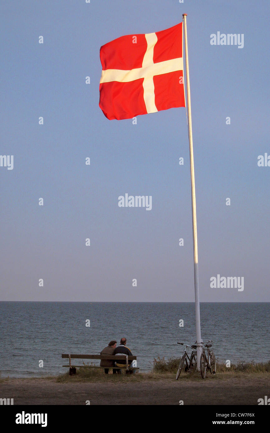 two people sitting on a bench near the danish national flag at the beach, Denmark, Bornholm, Soemarken - Stock Image