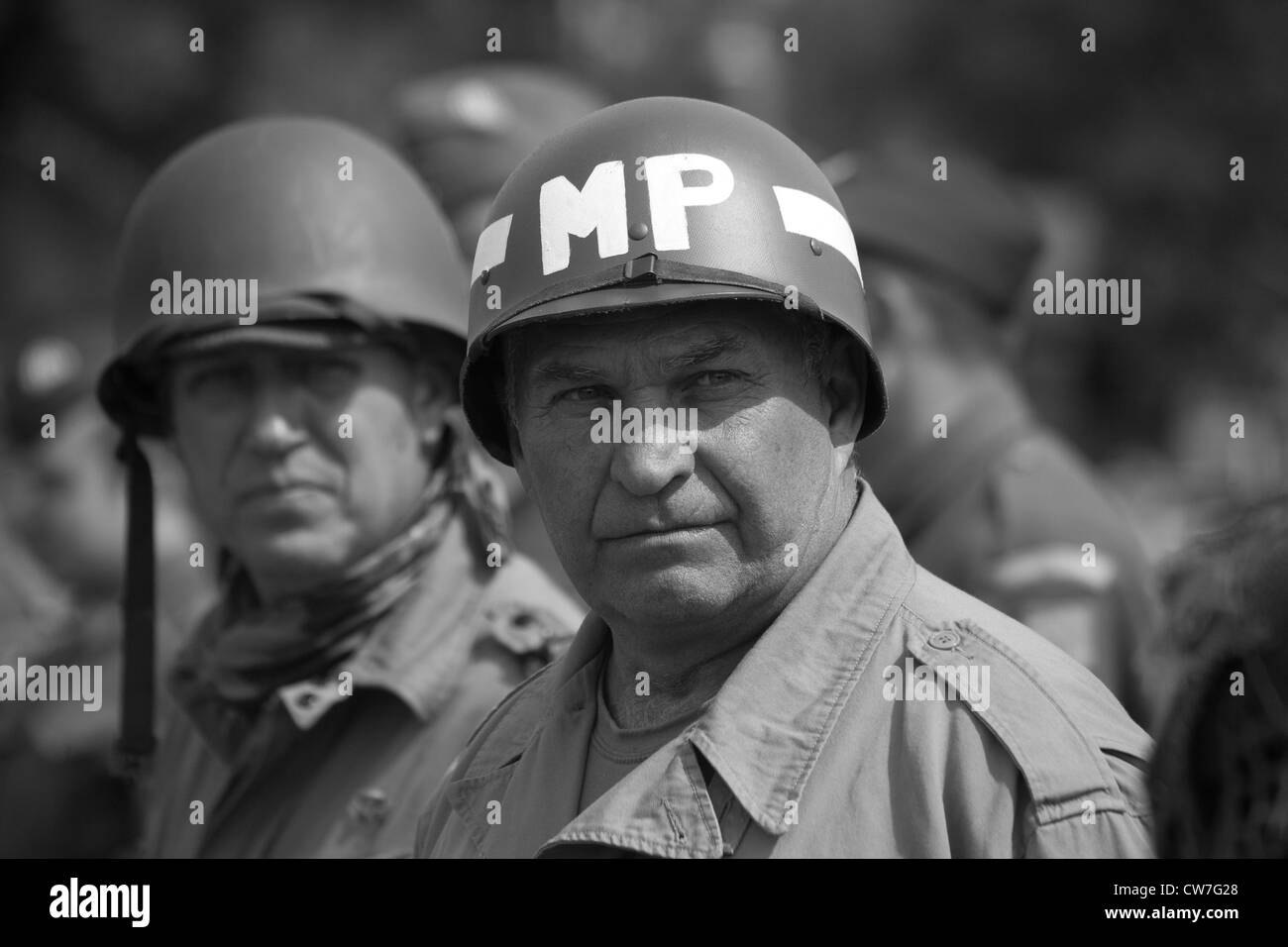 Re-enactor playing 1940's American Soldier with others - Stock Image