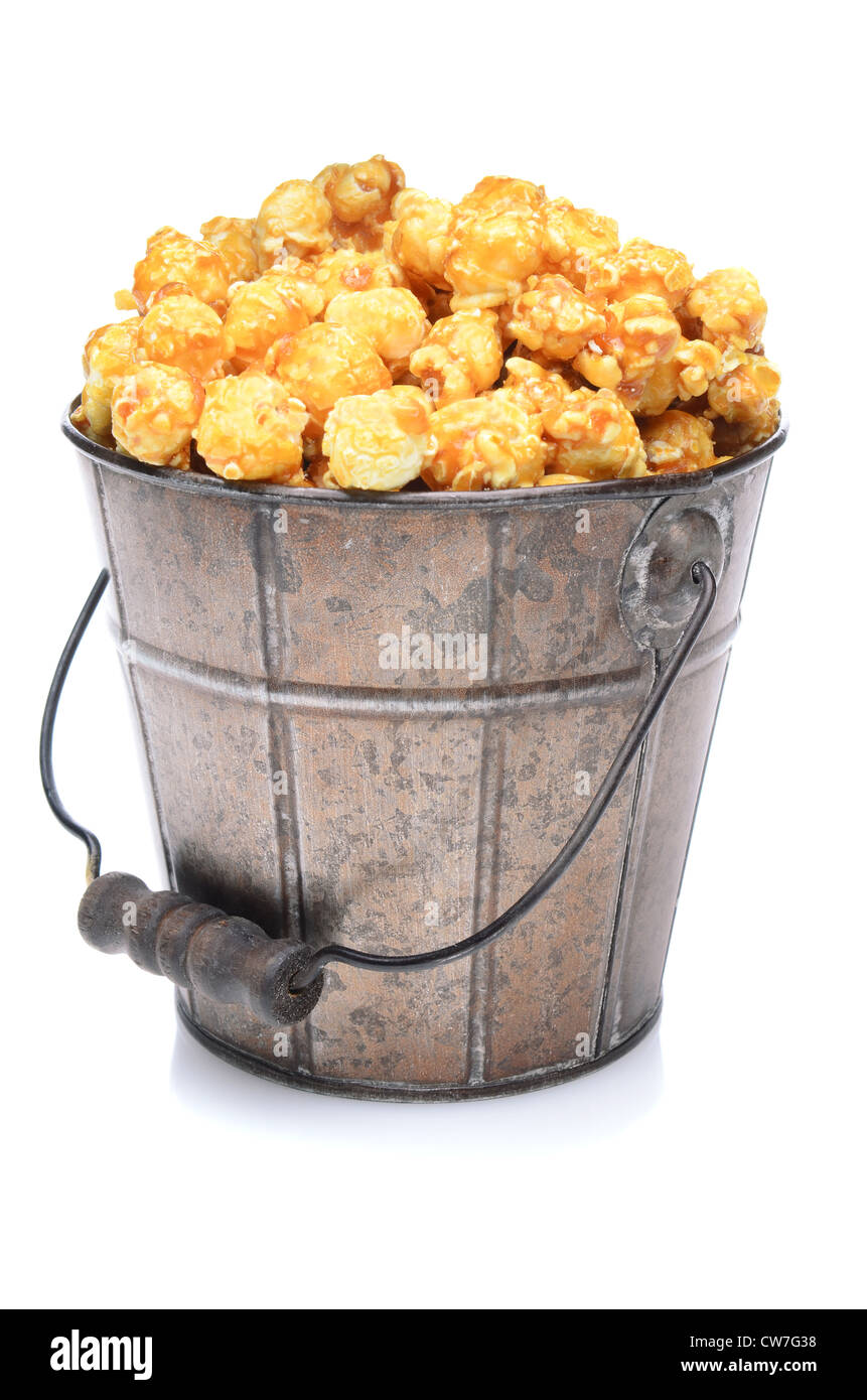 A old fashioned bucket of caramel corn over a white background with slight reflection. - Stock Image