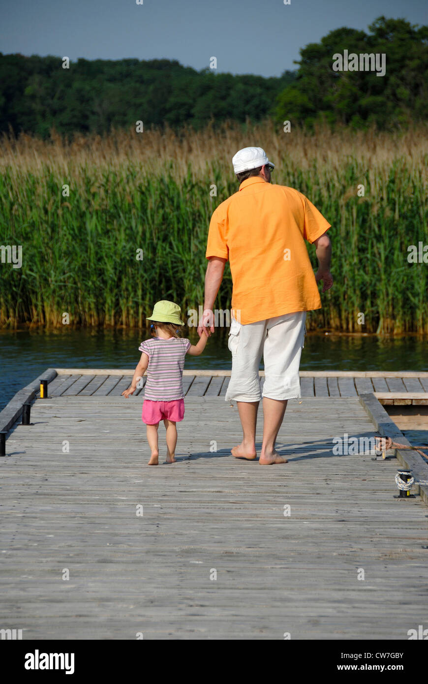 little child and grown up going about a boardwalk - Stock Image