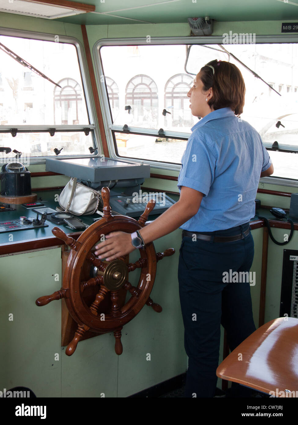 Female driver operating a vaporetto - Stock Image