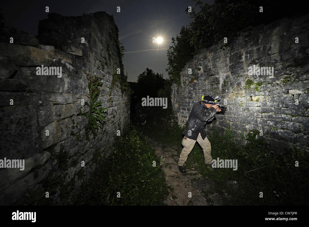 photographer in the castle ruin of Dvigrad at full moon searching geckos, Croatia, Dvigrad - Stock Image