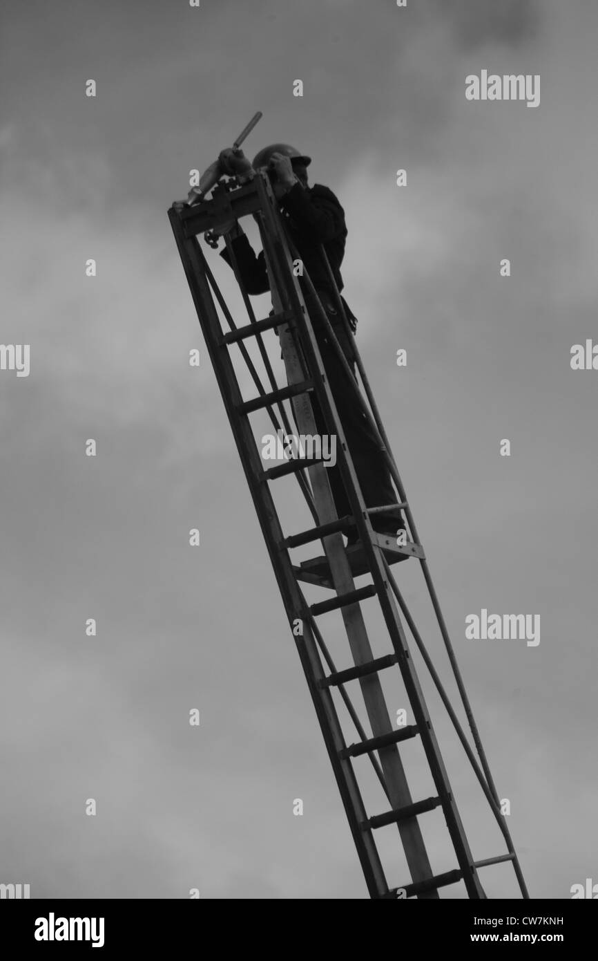 Member of the 1940's National Fire Service on ladder with water jet/hose - Stock Image