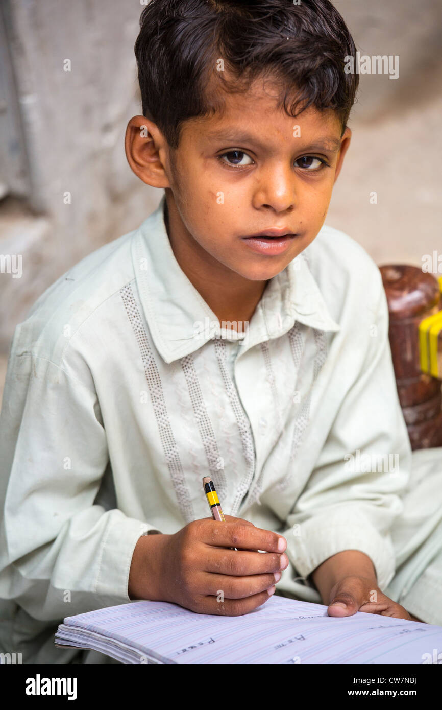 Young Pakistani boy writing english in Said Pur Village, Islamabad, Pakistan - Stock Image