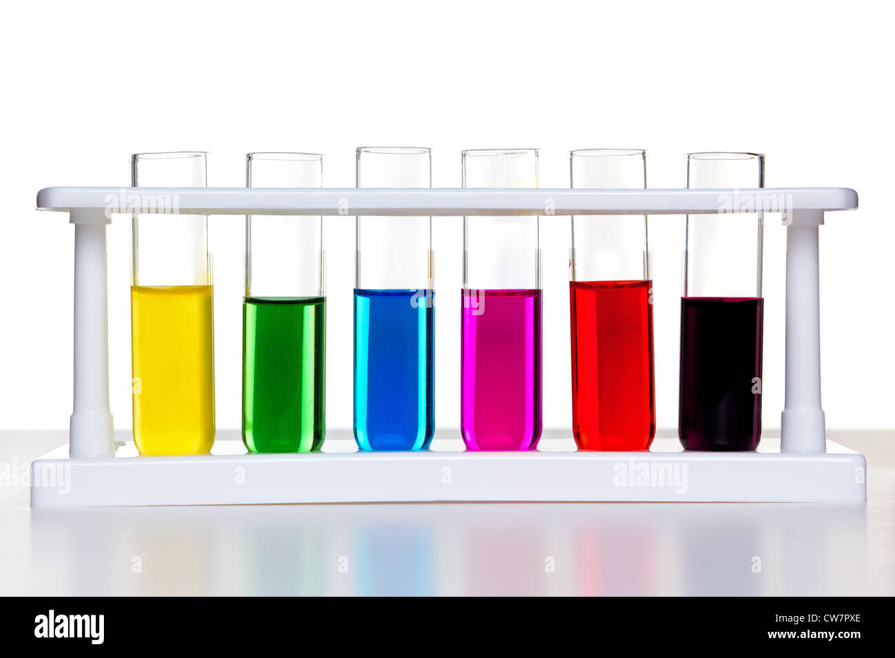 Photo of test tubes full of chemicals in a rack on a white background. - Stock Image