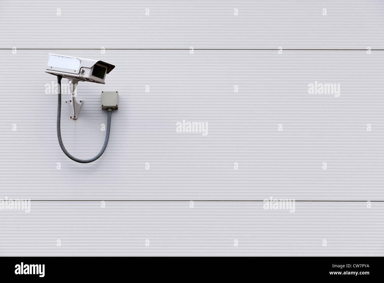 Photo of a CCTV security camera on the wall of a building with copy space for text. - Stock Image